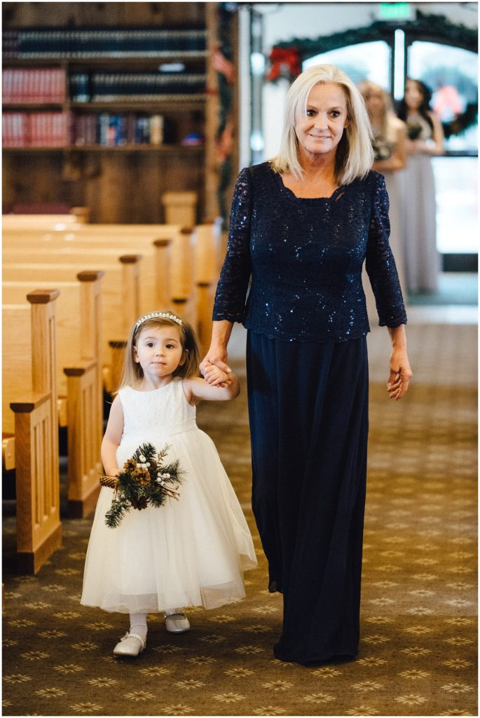 Brides mom with bride and grooms daughter walking down the aisle