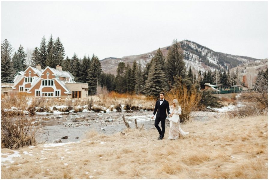 Bride and groom out for a walk on a beautiful day in the snowy Colorado Rockies in Vail Colorado