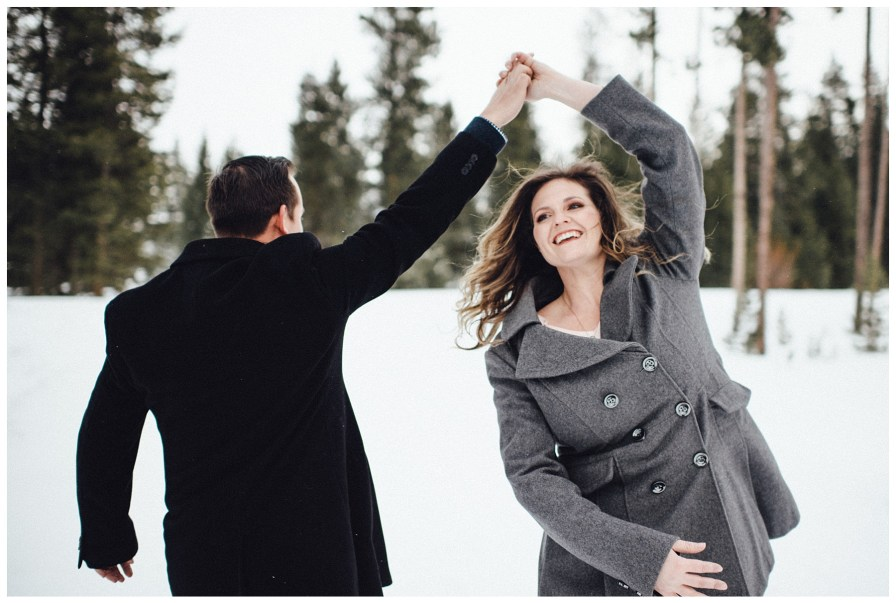 Couple dancing in the snow during engagement photos