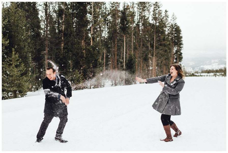 Adventurous couple has snowball fight during engagement photos in Winter Park Colorado