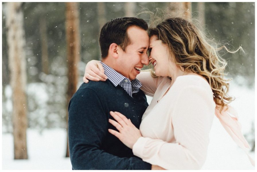 Adventurous couple hikes a mountain to take snowy engagement photos