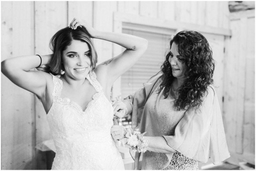 bride's mom zips up bride's dress