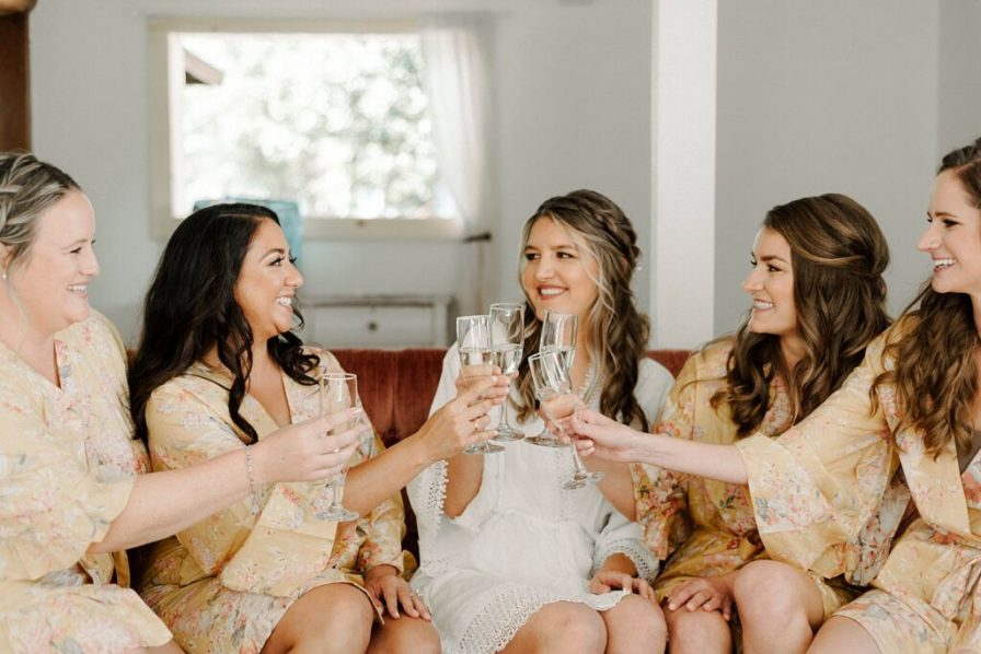 bride and bridesmaids toasting champagne