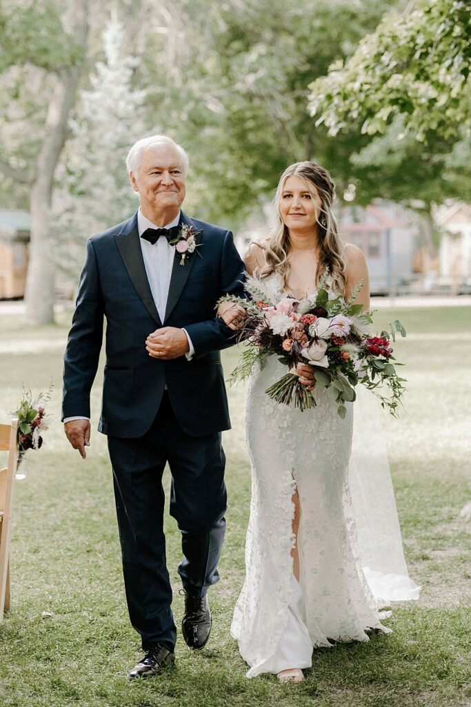 father walks his daughter down the aisle during this River Bend summer wedding