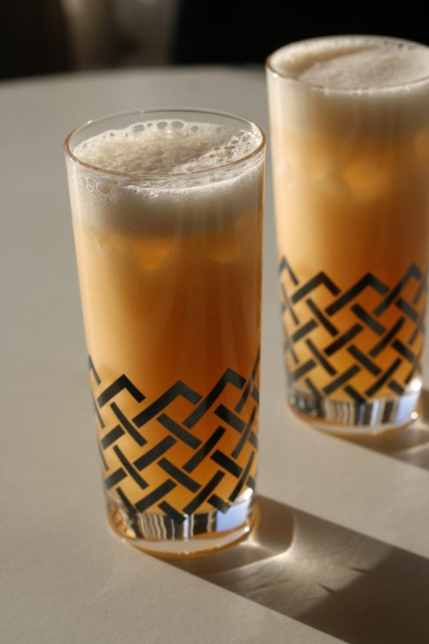 Two tall cocktails in glasses with a platinum basket weave design.