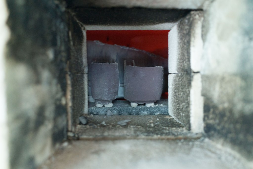 Two cups glazed with a high-iron (50% iron oxide, 50% wood ash) glaze, as viewed through a small spyhole at the rear of the woodfired kiln. These are intended for 'hikidashi', which means that they will be pulled from the kiln when red hot (1300 degrees Celsius) and cooled in a bucket of water. This treatment endows them with a luscious matte black surface.
