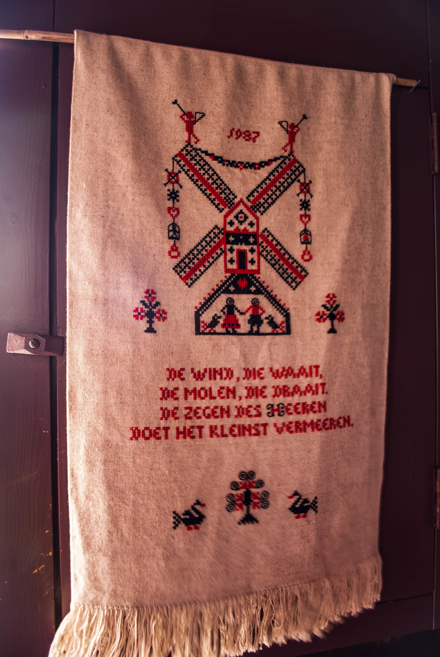 Embroidery hanging in one of the windmills. Rough translation: 'The wind that blows, the mill that turns, the blessing of the Lord that makes the small increase.'