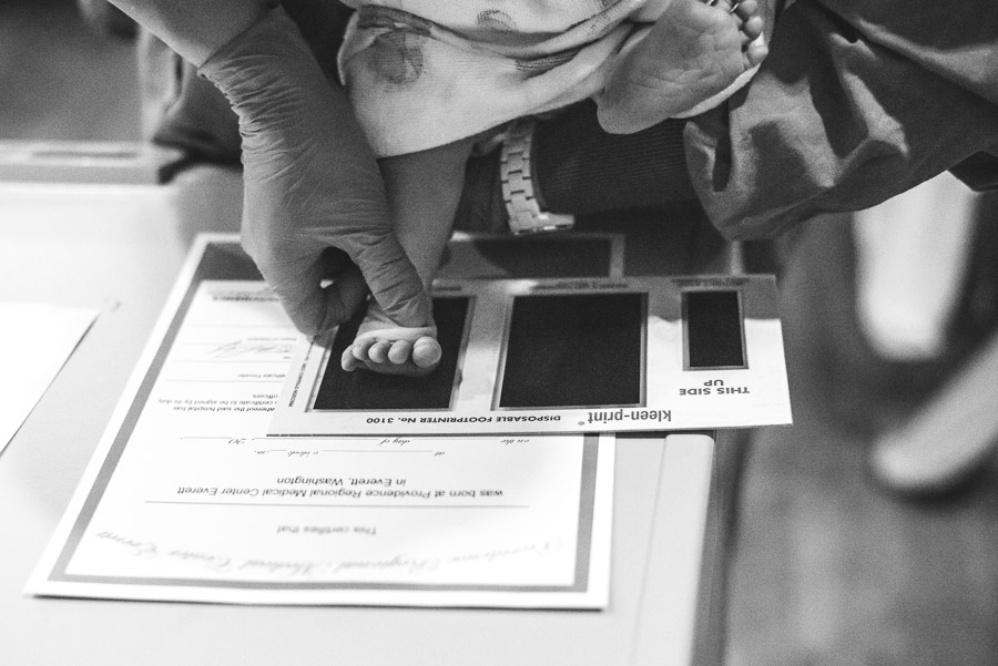 A nurse placing a newborn baby's foot into an ink pad.