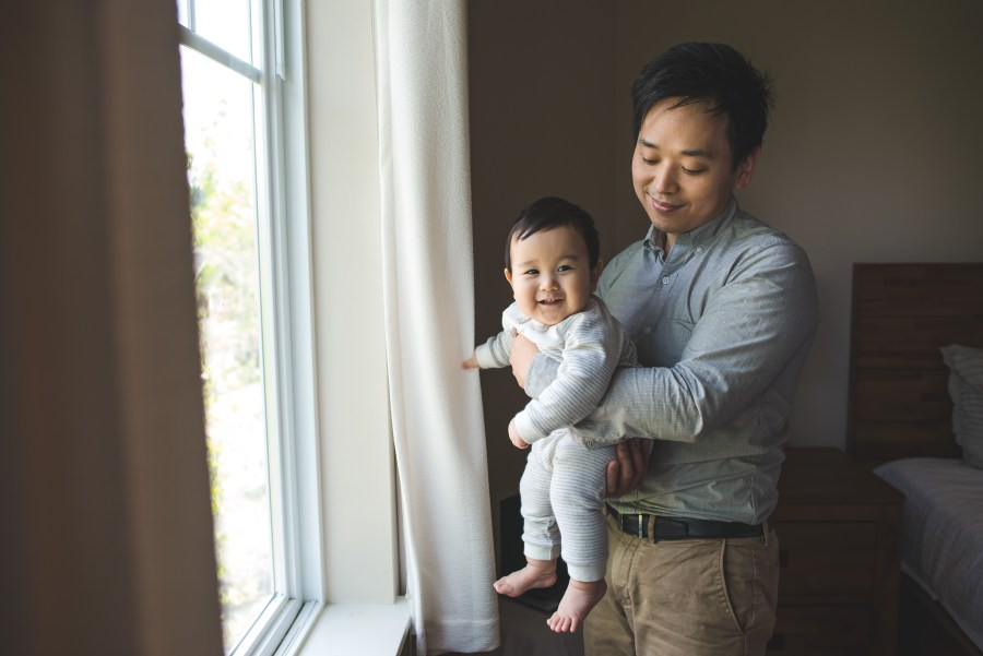 Father holds son in front of a bright window