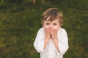 Boy covering his face while laughing at Seattle family photographer and Issaquah family photographer