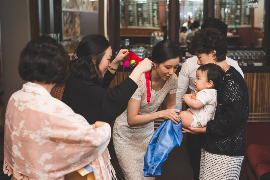Baby being dressed in traditional Korean first birthday garments
