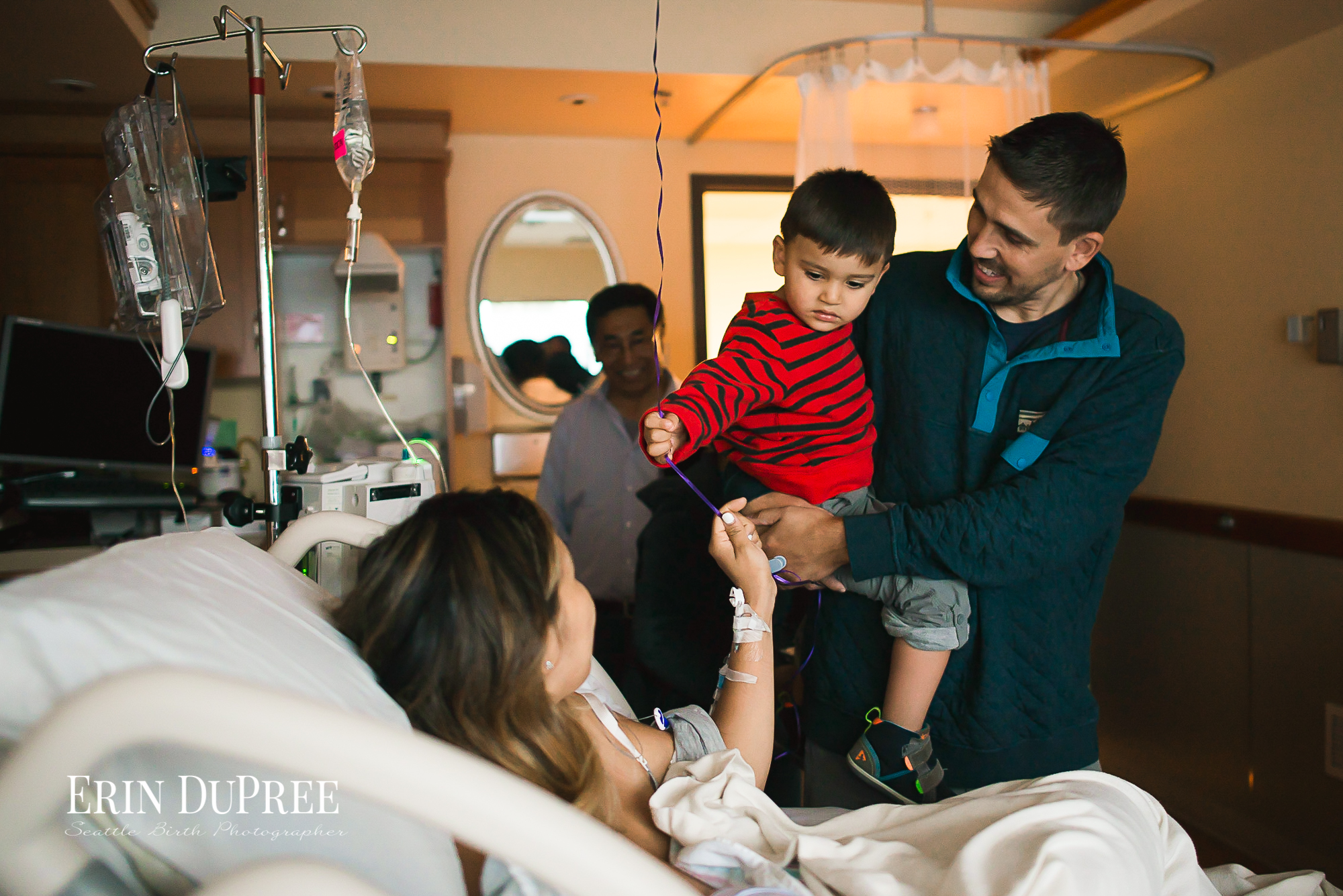 Father holding son by hospital bed by Seattle Birth Photographer