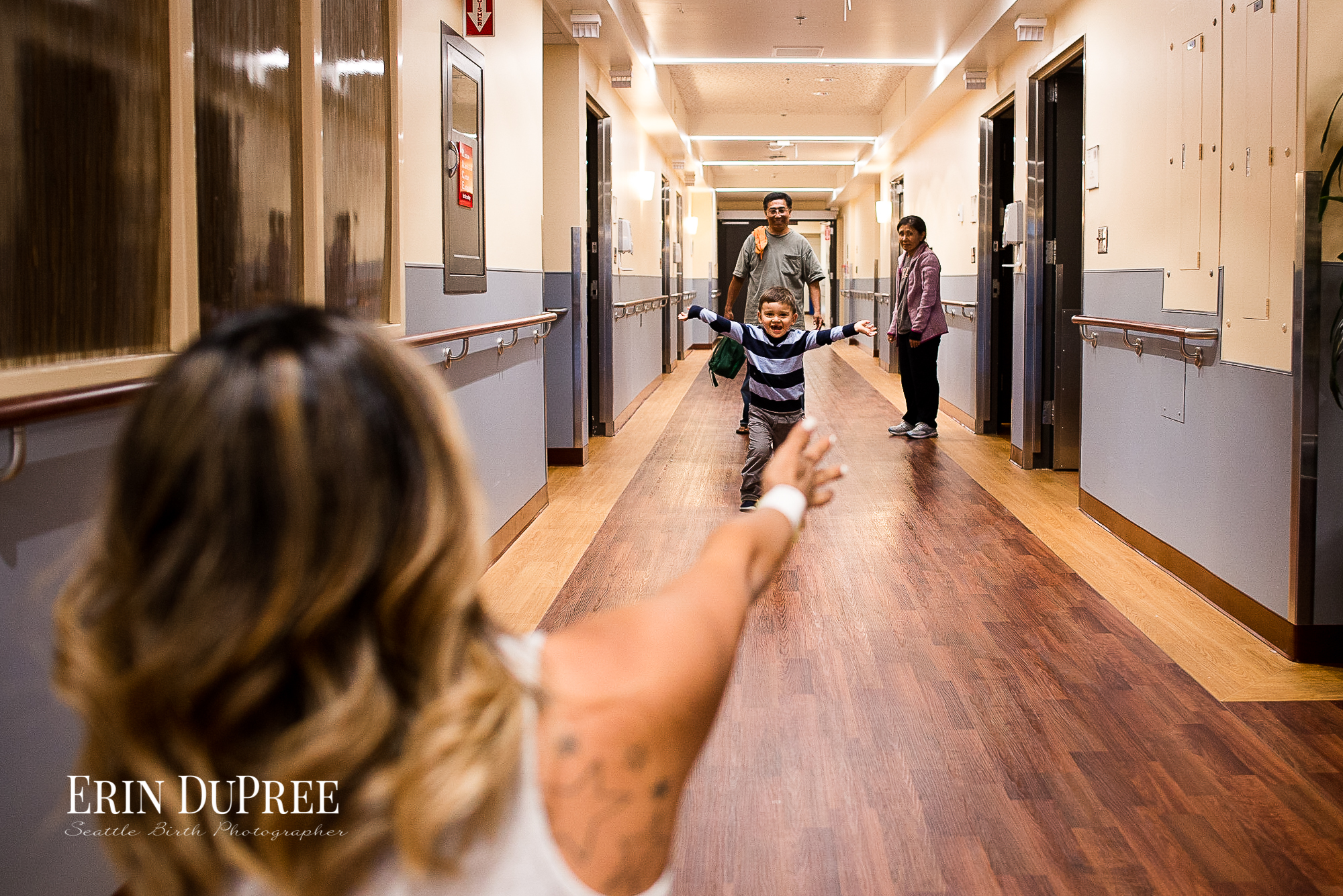Son running to his mom with open arms in hallway by Seattle Birth Photographer