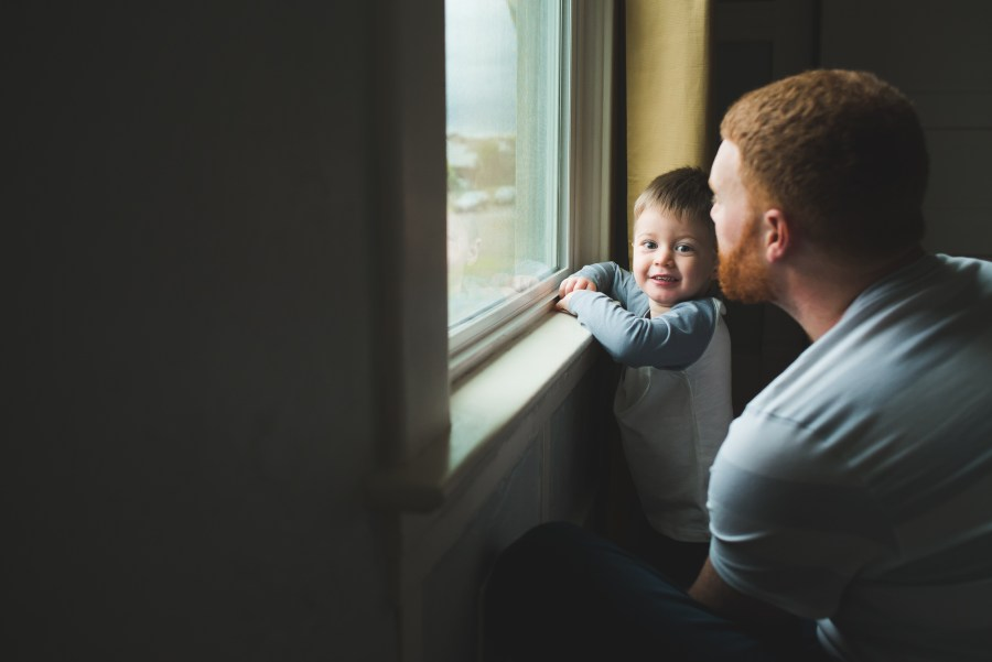 Toddler boy and father by a window by Seattle Newborn Photographer
