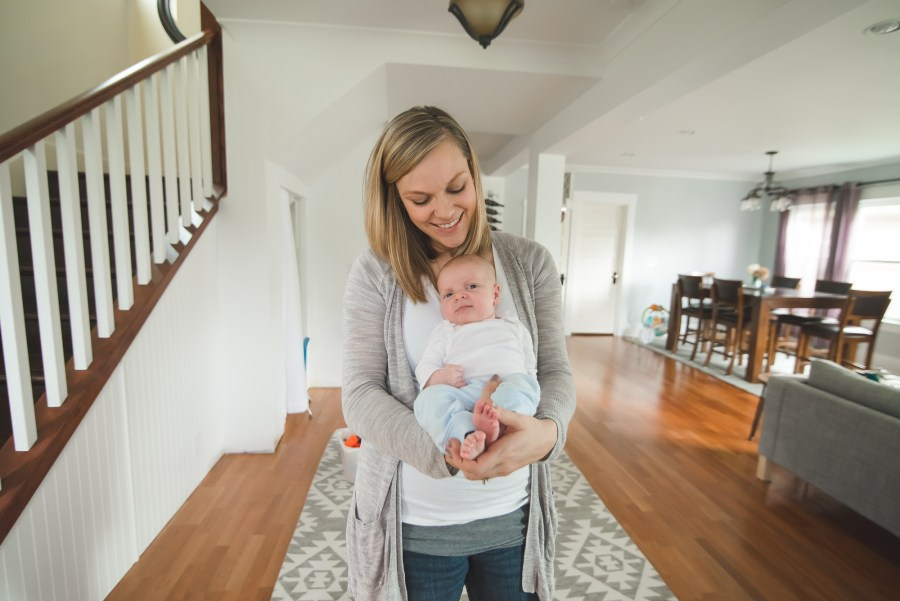 Mother holding newborn baby inside home by Seattle Newborn Photographer