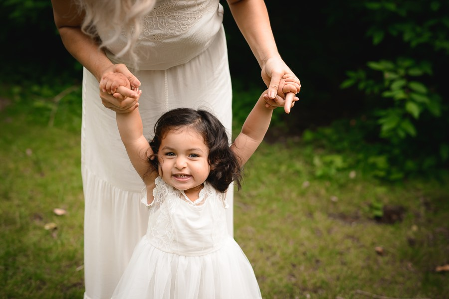 Professional family portrait of a young girl in a white dress holding her mother's hands