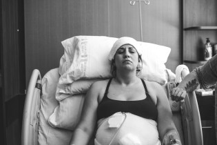A woman lying in a hospital bed while laboring, in intense concentration, with a wet rag across her forehead.