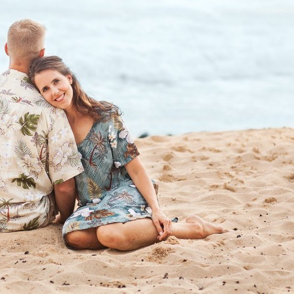 couple sitting in sand on beach on Kauai with man facing away and woman looking at the camera