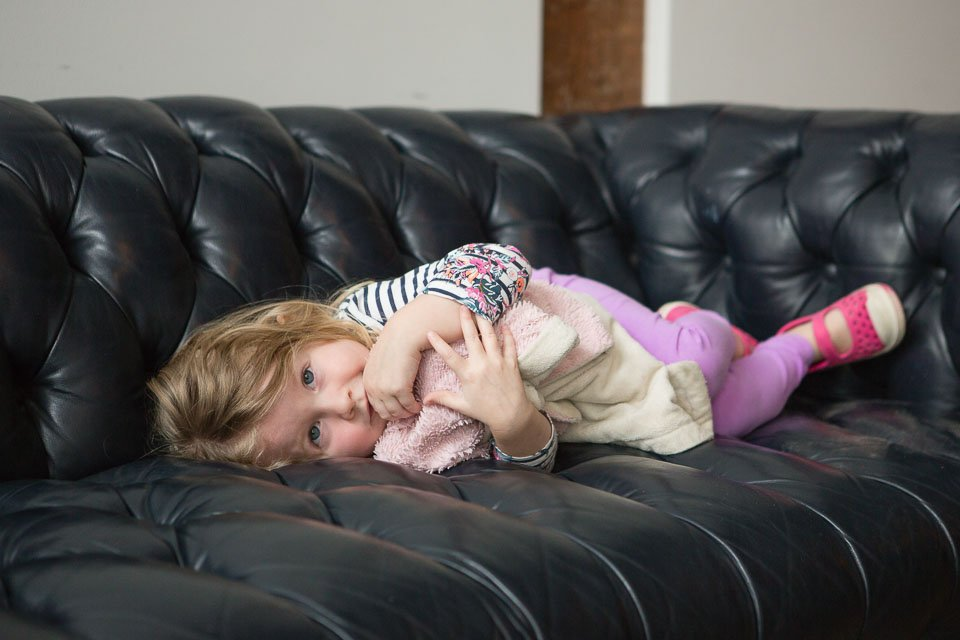 little girl with blanket laying on a couch