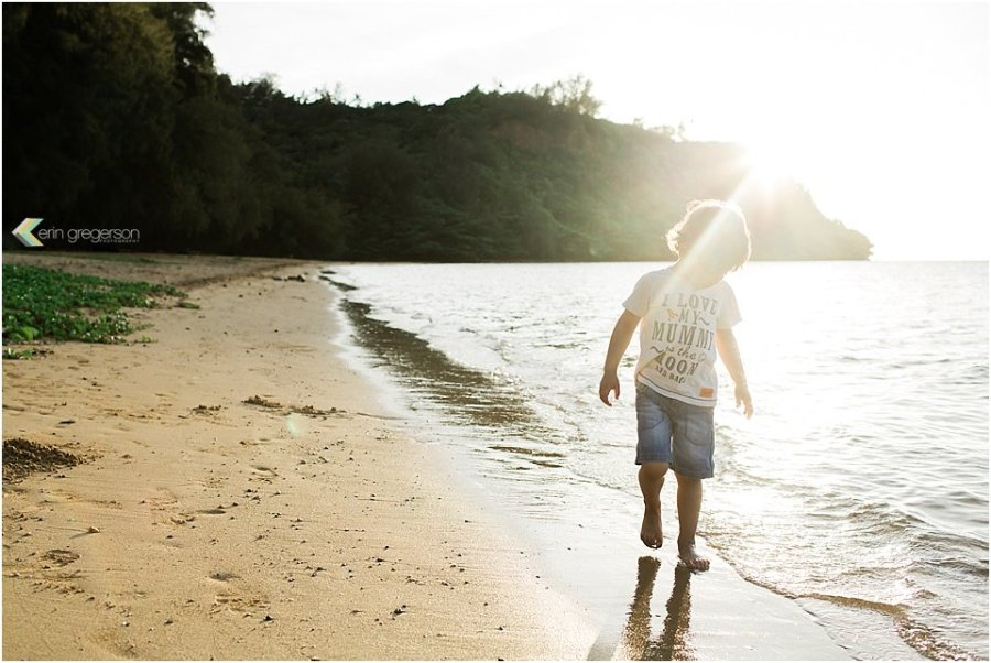 young boy walking on beach with green mountains and beautiful light on Kauai