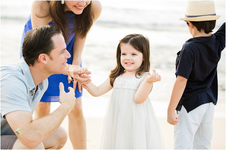 family of four laughing at little girl on Kauai beach