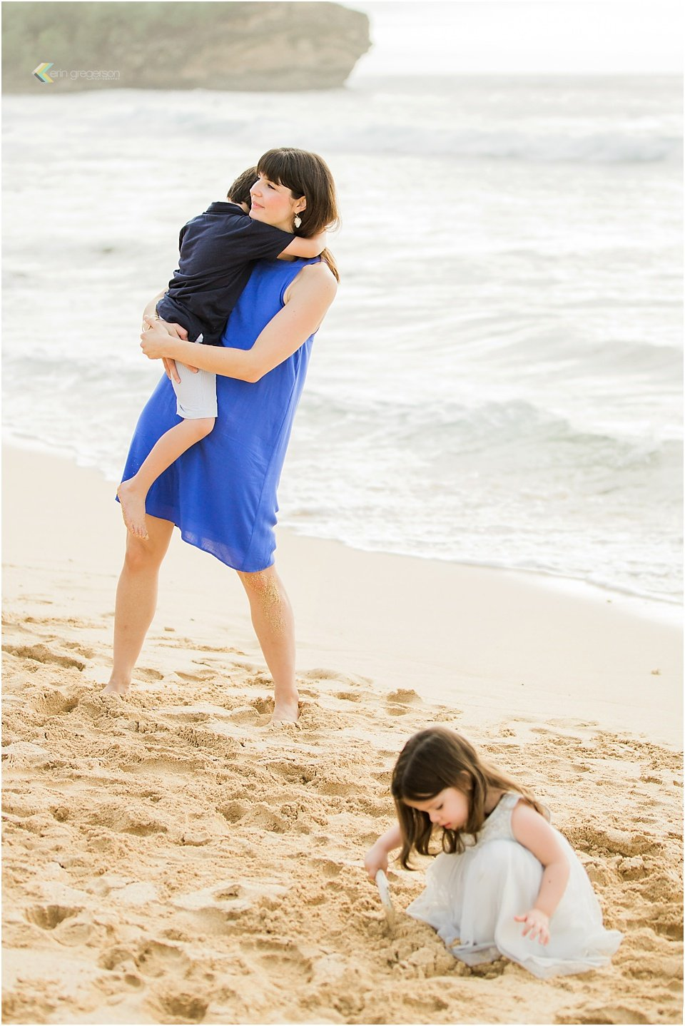 Mother holding son while young daughter is playing in the sand Kauai