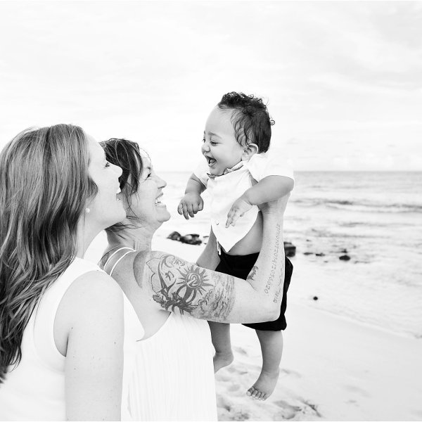 Black and white image of lesbian couple with their little baby boy playing on Kauai beach in family photo