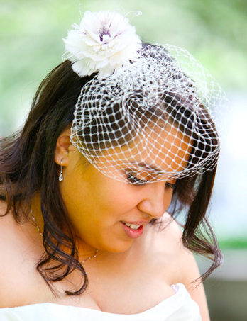irene wore a custom feather fascinator with color accents, paired with an elegant net birdcage veil
