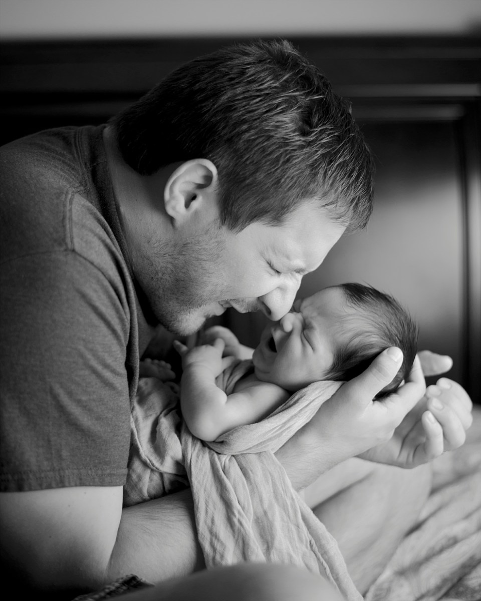 Father with newborn during in home lifestyle newborn session in Fairfax VA by Erin Tetterton Photography