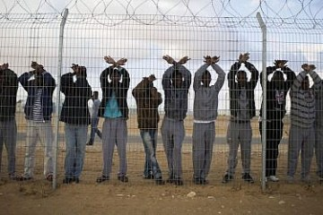 Asylum seekers raise hands in protest in detention centre