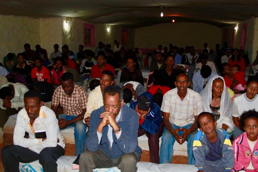 Dr Berhane Asmelash praying at a church in a refugee camp in Ethiopia