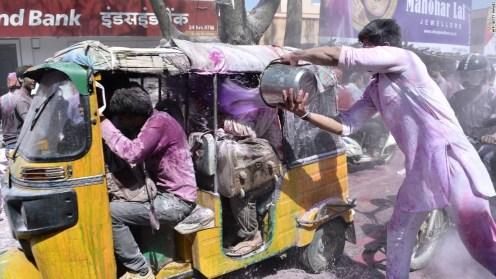 Un hombre echa una cubeta llena de color a un carro con gente en Mathura, India