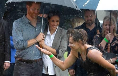 Meghan Markle cubre a Harry de la lluvia