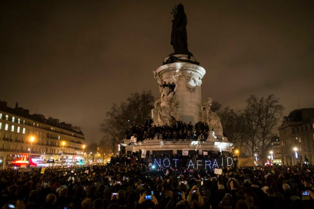 epa04550028 A sign reads 'Not Afraid' as thousands gather for a candle light vigil on Place de la Republique in central Paris hours after the attack by two gunmen on the 'Charly Hebdo' headquarters in Paris, France, 07 January 2015. According to news reports, 12 people have been killed in a shooting attack at satirical French magazine Charlie Hebdo in Paris. EPA/IAN LANGSDON