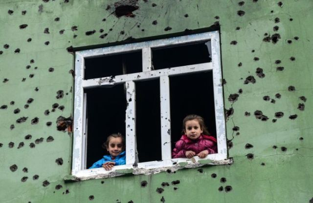 Children look out from a window of an bullet-scarred house in the kurdish town of Silopi, in southeastern Turkey, near the border with Iraq on January 19, 2016.  Turkey is waging an all-out offensive against the separatist Kurdistan Workers' Party (PKK), with military operations backed by curfews aimed at flushing out rebels from several southeastern urban centres.  / AFP / ILYAS AKENGIN