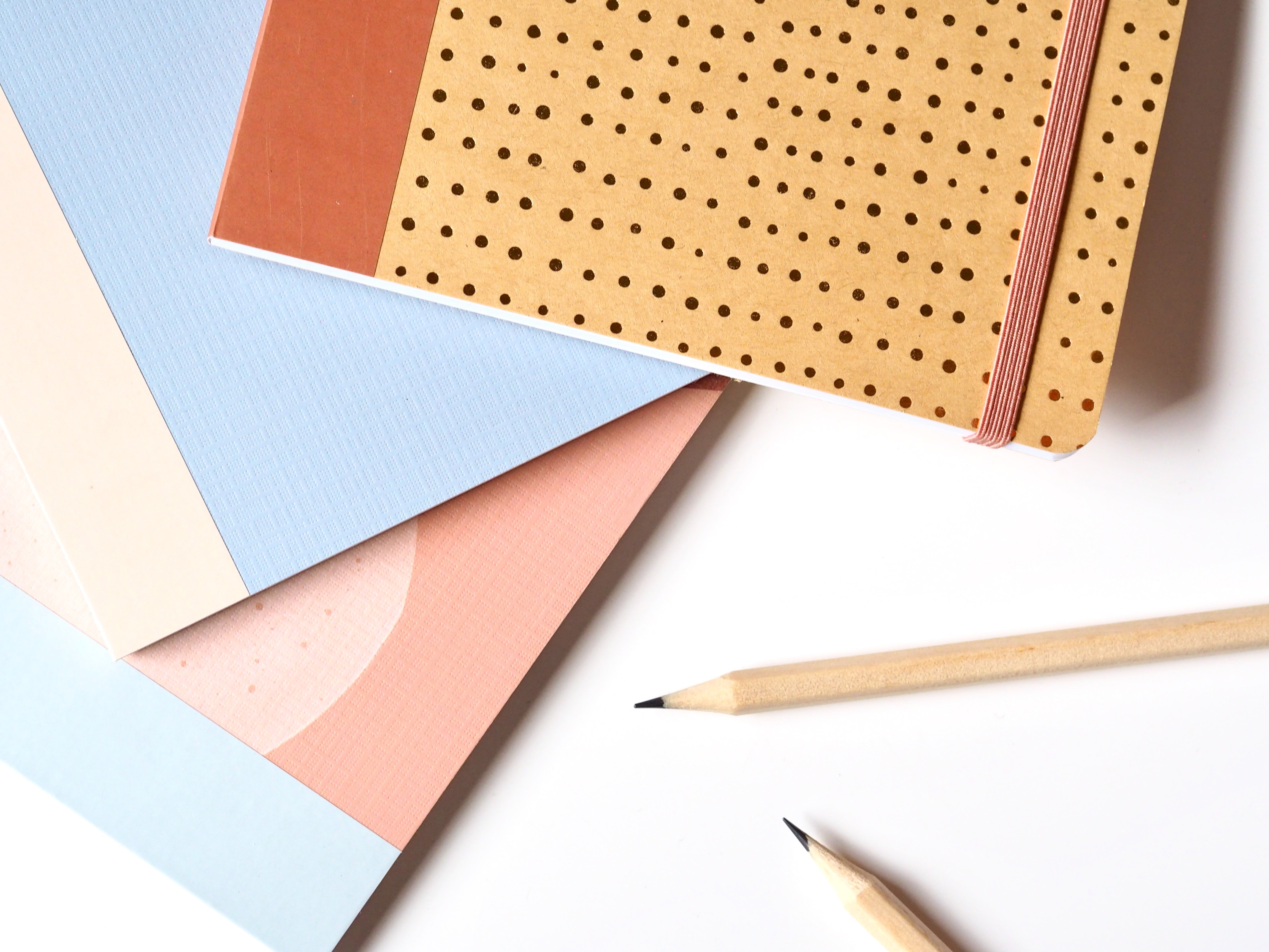 close up of colorful stationery next to pencils