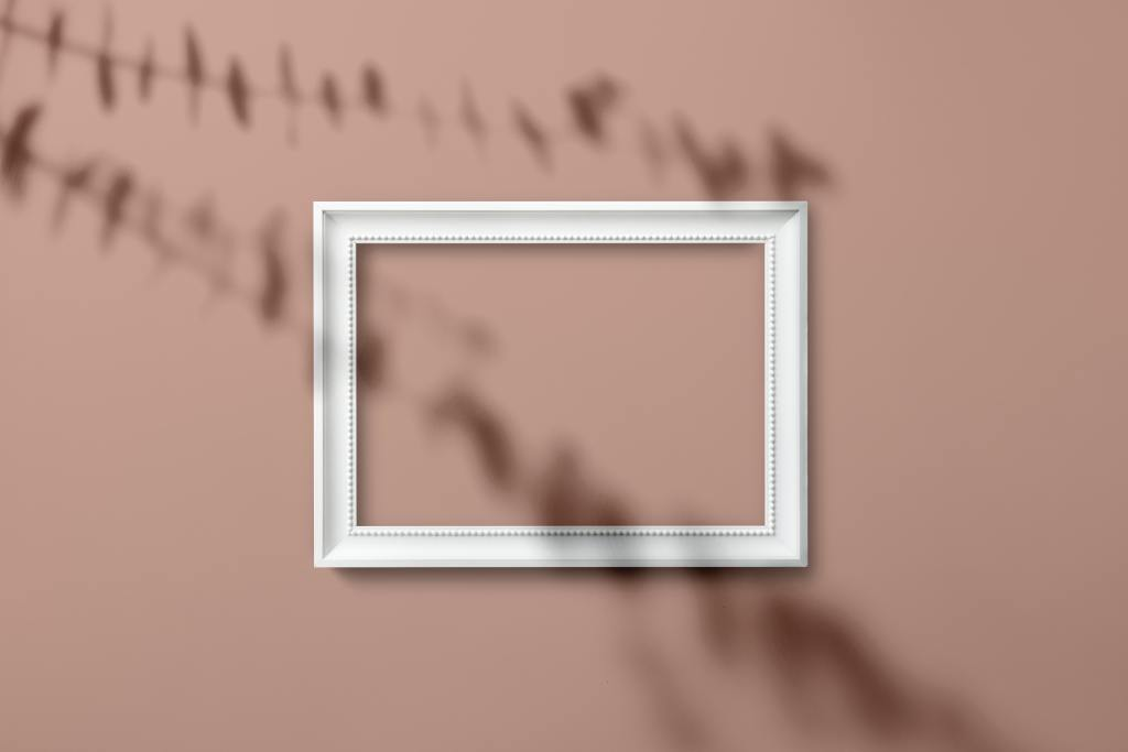empty white frame hanging on pink wall