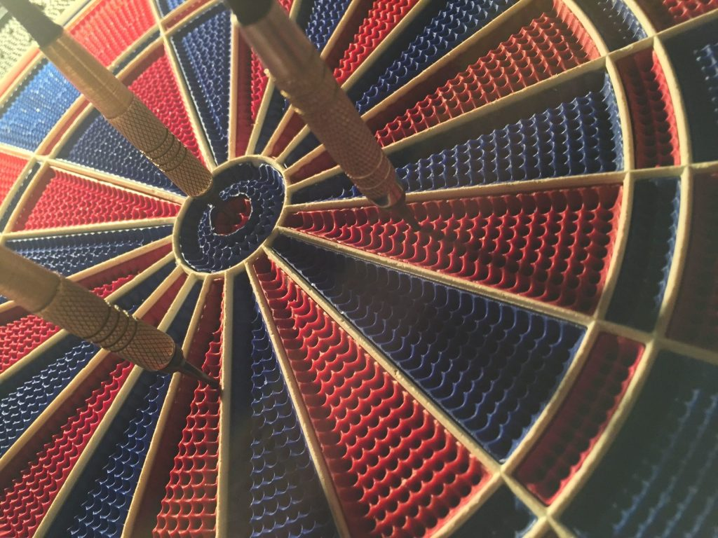 three darts close the center of a dart board