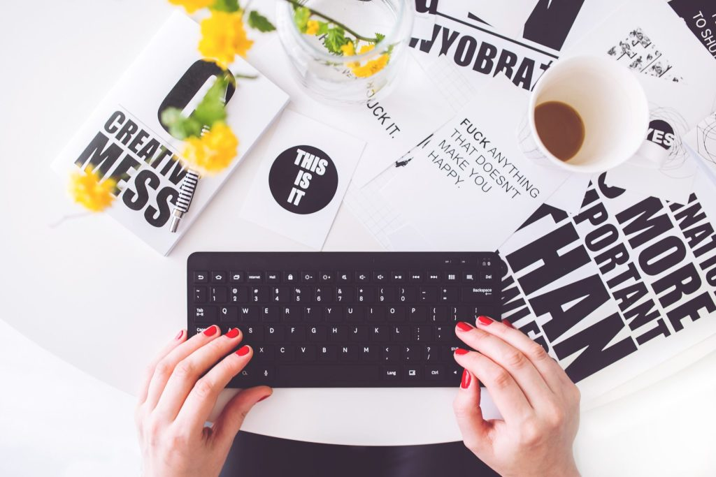 black keyboard surrounded by papers and a coffee mug
