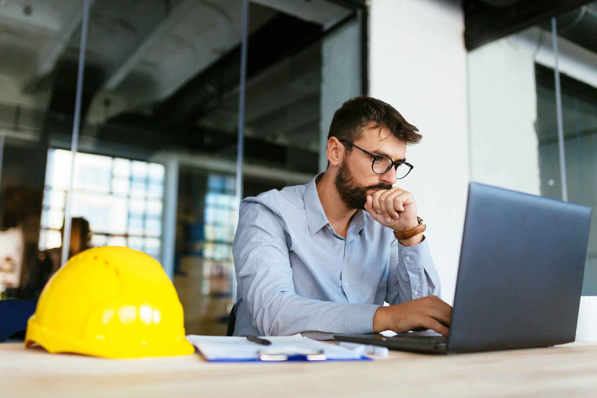 man thinking of blog topics on computer with yellow hard hat on the desk