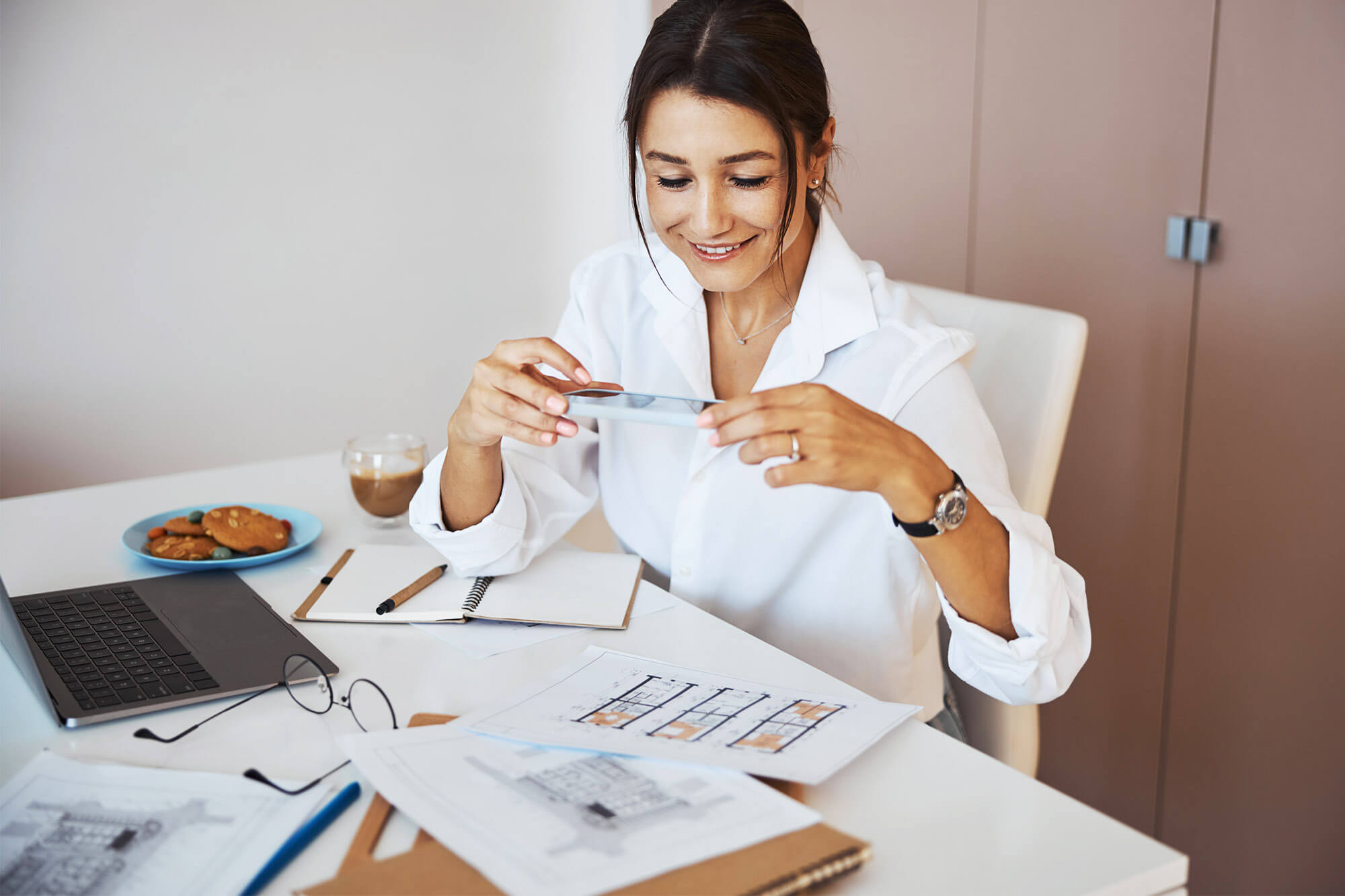 a woman in a white blouse has papers spread across desk and takes picture of it with phone