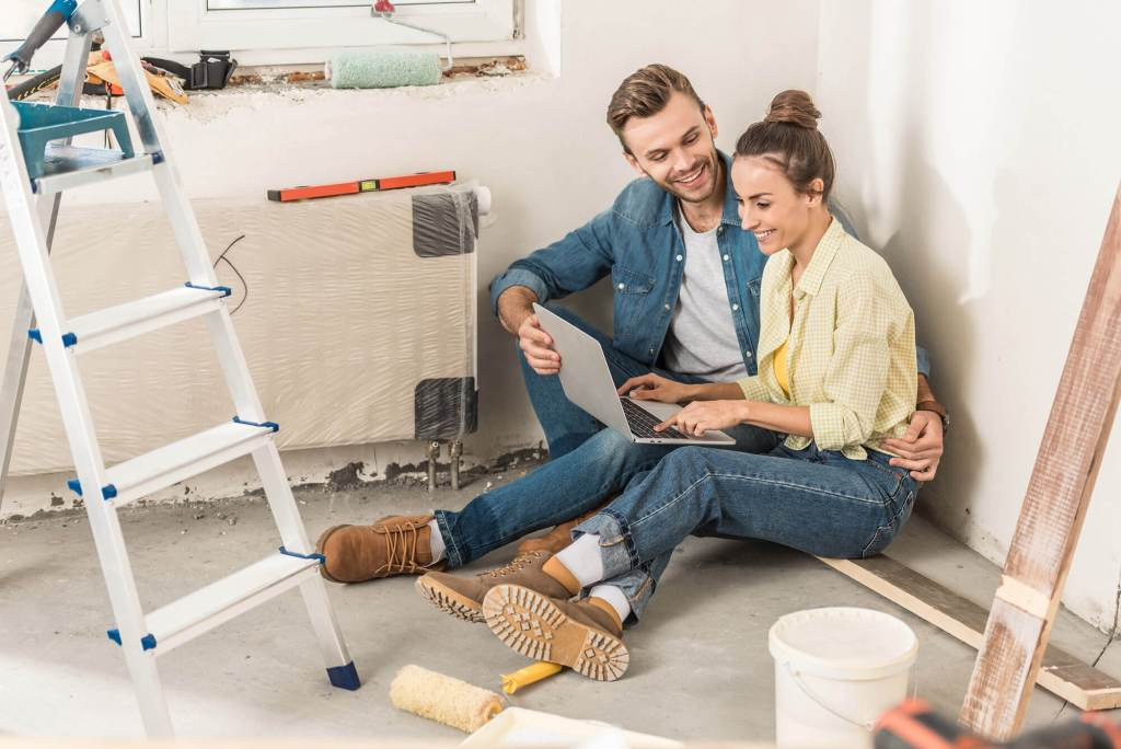 A man and a woman smile while browsing online for a contractor