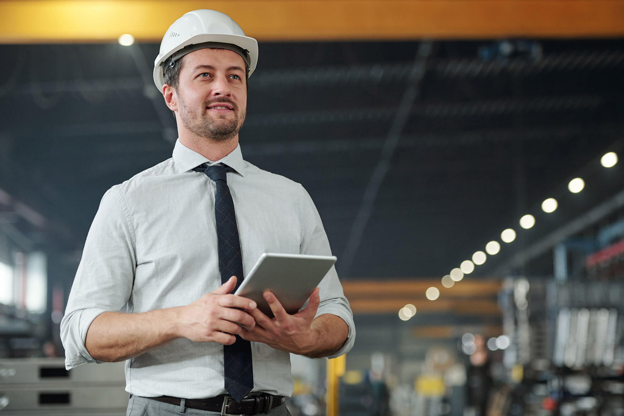 Man in white shirt with black tie and white hard hat walks through building with note pad