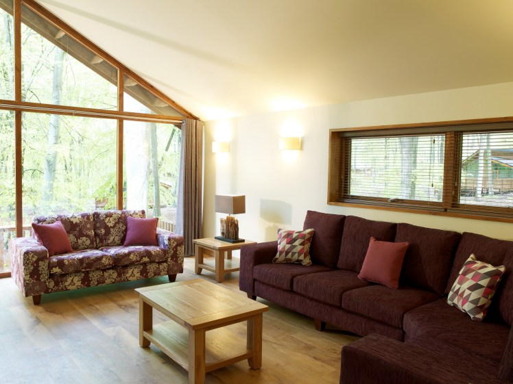 Lounge area at a Forest Holidays lodge, with panoramic feature window