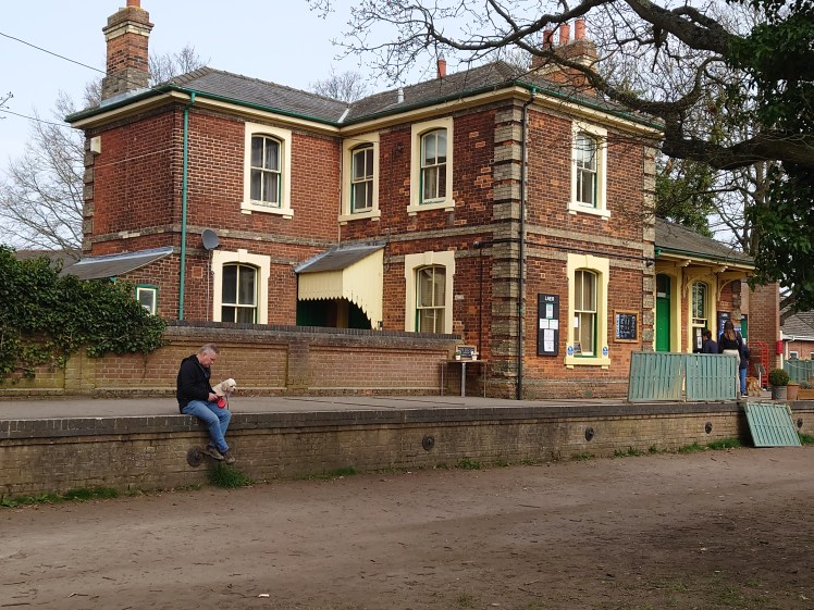 A man and his dog sit on the former platform outside the Booking Hall Cafe in Rayne
