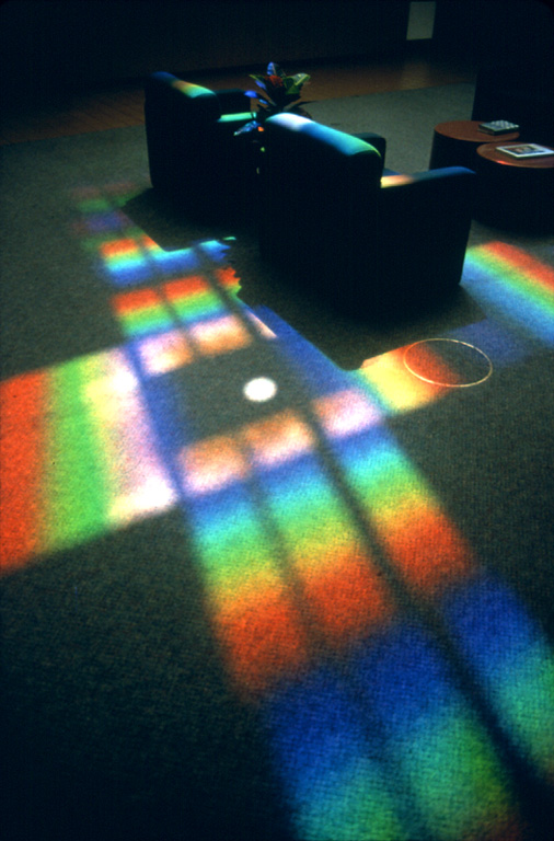 large cross of rainbow light projected on floor by prism