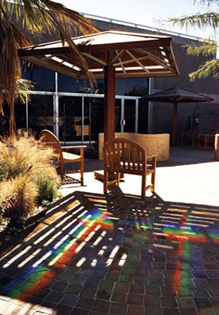 Rainbow light pattern projected from Erskine's prisms installed in the wooden shade umbrellas in the Healing Garden