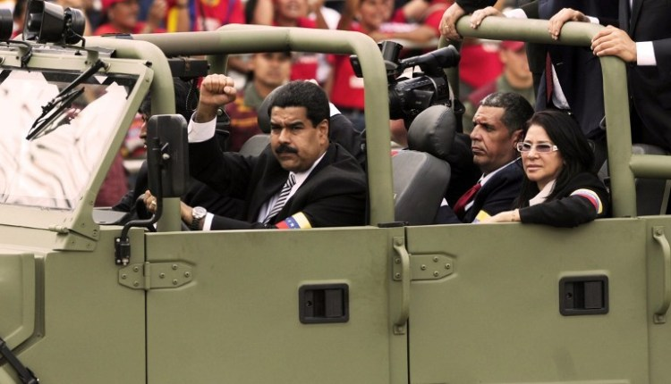 Venezuelan acting president Nicolas Maduro(L) clinches his fist next to his wife Cilia Flores(R) while they attend the funeral of late Venezuelan President Hugo Chavez is taken from the Military Academy to former 4 de Febrero barracks in Caracas, on March 15, 2013. The body of Chavez was moved Friday to the barracks in a final march to honor of the leftist leader a month before elections are held to pick his successor. The Caracas military academy, where Chavez's casket has been on view, served as the starting point for the procession escorting the remains of the 58-year-old, who last week succumbed to cancer after 14 years in power.  AFP PHOTO/LEO RAMIREZ