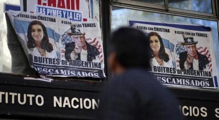 Imagen de archivo de una persona pasando frente a unos afiches de la presidenta de Argentina, Cristina Fernández, y otro del juez estadounidense Thomas Griesa, representado como el Tío Sam, pegados cerca del Congreso en Buenos Aires