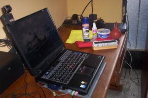 Laptop negra e insumos de limpieza al costado.